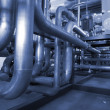 Pipes, tubes, machinery and steam turbine at a power plant in bl — Stock Photo