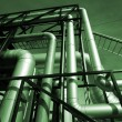 Pipes, bolts, valves against blue sky in green tones — Stock Photo