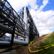 Industrial pipelines on pipe-bridge against blue sky — Stock Photo
