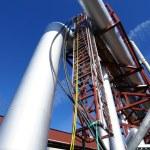 Industrial pipelines on pipe-bridge against blue sky — Stock Photo #6923887