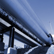 Industrial pipelines on pipe-bridge against blue sky — Stock Photo #6925391