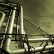 Industrial pipelines on pipe-bridge against sky - Stock Photo