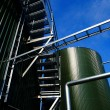 Industrial zone, Steel pipelines and tanks against blue sky - Stock Photo