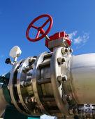Zona industrial, tubulações de aço e válvula no céu azul — Foto Stock