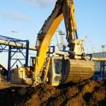 Hydraulic excavator at work. Shovel bucket against blue sky — Stock Photo #6952081
