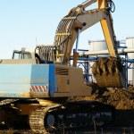 Hydraulic excavator at work. Shovel bucket against blue sky — Stock Photo #6952108