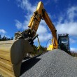 Hydraulic excavator at work. Shovel bucket against blue sky — Stock Photo #7489174