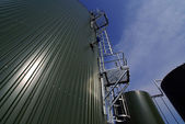 Industrial pipelines and tanks against blue sky — Stock Photo