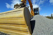 Hydraulic excavator at work. Shovel bucket against blue sky — Stock Photo