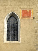 Anciant church window with sun dial on a stone wall — Stock Photo