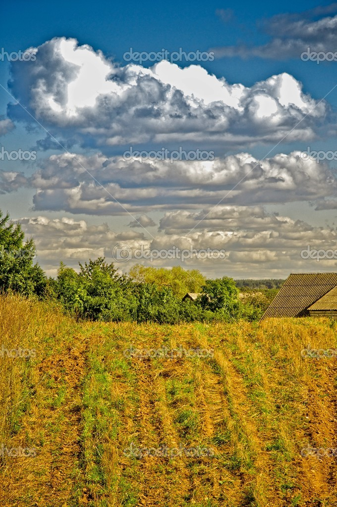 Typical rural landscape; a field underneath clouds that pass by. — Stock Photo #7204314
