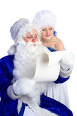 Santa Claus in blue reading list of presents — Stock Photo