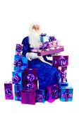 Santa Claus sitting with lots of presents — Stock Photo