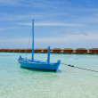Blue boat anchoring on tropical beach — Stock Photo