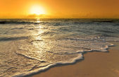 Caribbean sunrise with wave on beach — Stock Photo