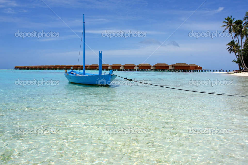 Blue boat anchoring under palm tree on the beach. In the background some over water bunglaows. — Stock Photo #7108831
