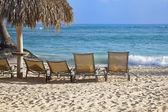 Four beach chairs against white sand — Stock Photo