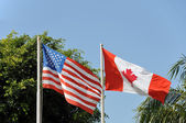 American and Canadian flags against blue sky — Stock Photo