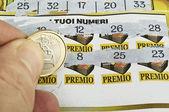 Een menselijke hand is een loterij ticket krassen — Stockfoto