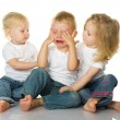Two little girls calm the crying boy. — Stock Photo
