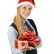 Businesswoman wearing a santa's hat with a gift — Stock Photo