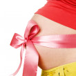 Abdomen a young pregnant woman tied with a Red ribbon — Stock Photo