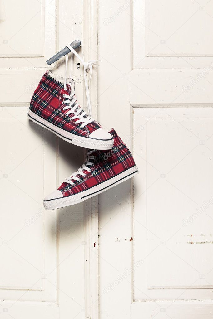 Red checkered sneakers hanging on door knob  Stock Photo #6936357
