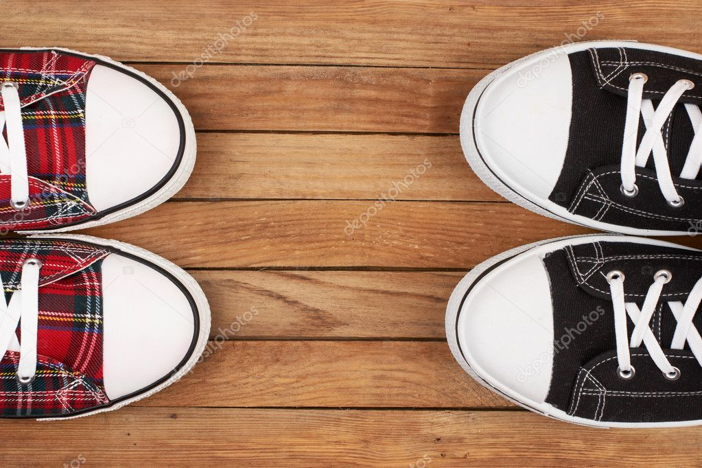 Two pairs of sneakers on wooden background  Stock Photo #6936389