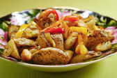 Roasted potatoes with vegetables in a plate — Stock Photo