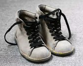 Winter shoes with yellow thread on gray background — Stock Photo