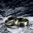Two golden wedding rings on ice surface - Zdjęcie stockowe