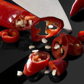Sliced chillies and blade — Stock Photo
