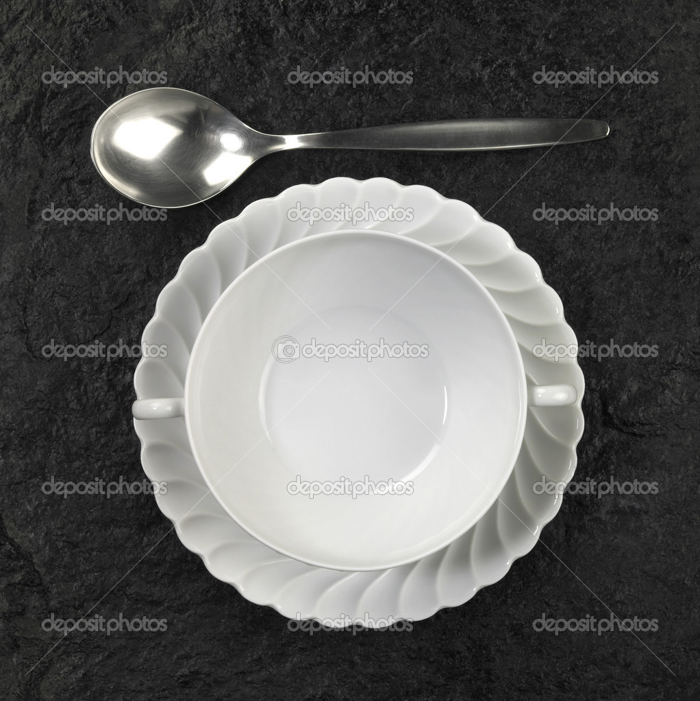 White porcelain soup plate and a spoon above on dark stone surface — Stock Photo #7128188