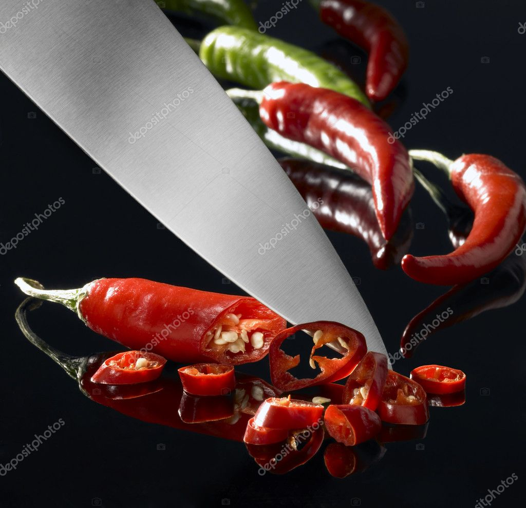 Studio shot of chili cutting with a big blade in dark back — Stock Photo #7128193