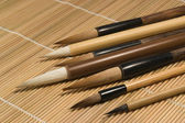 Chinese brushes on wooden mat detail — Stock Photo