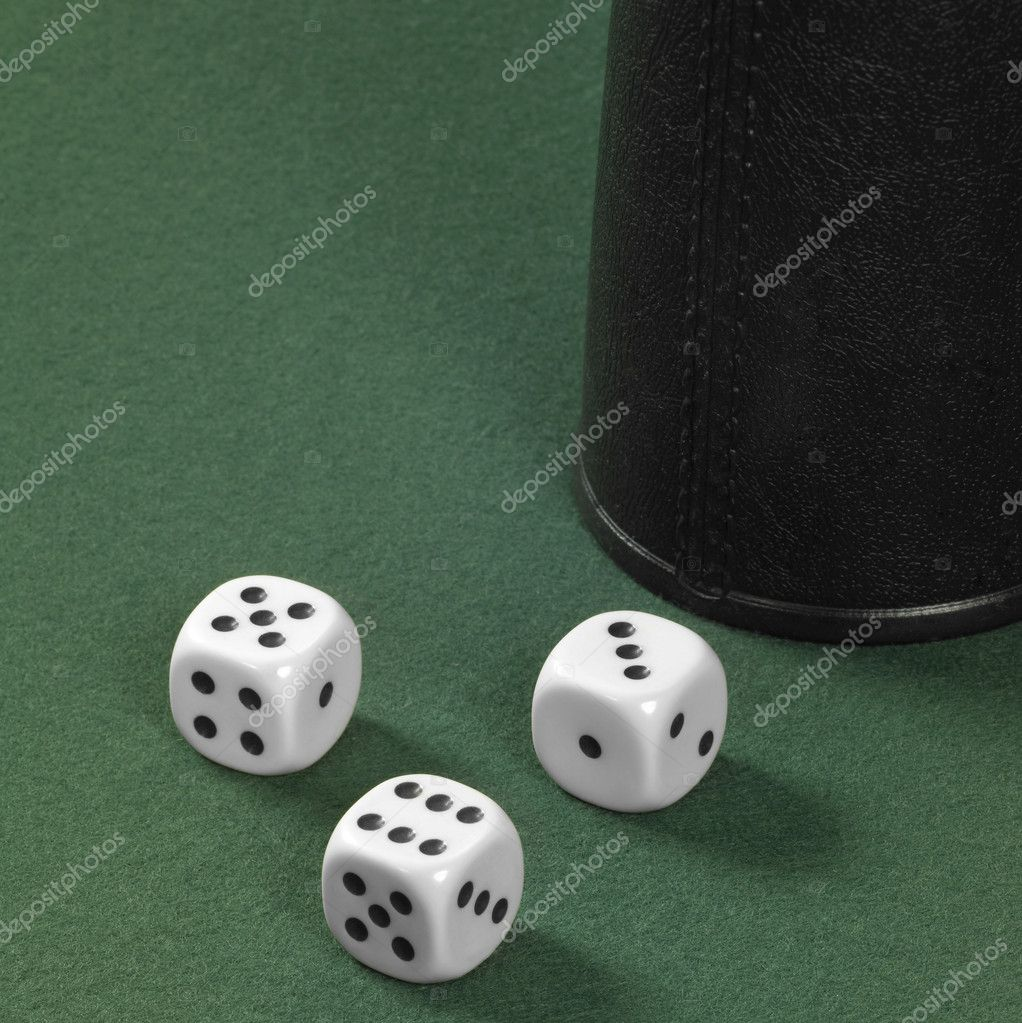 Gambling background with three dice and dice cup on green felt — Stock Photo #7139740