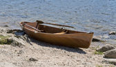 Wooden rowboat waterside — Stock Photo