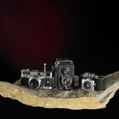 Nostalgic cameras on stone surface — Stock Photo