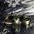 Stock Photo: Two golden wedding rings on ice surface