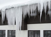 Icicles and house facade — Stock Photo