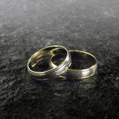Two golden wedding rings on stone surface — Stock Photo