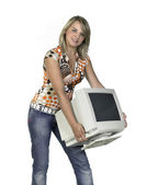 Cute girl carrying a computer monitor — Stock Photo