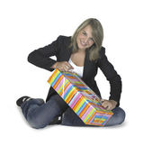 Sitting girl unwrapping a present — Stock Photo