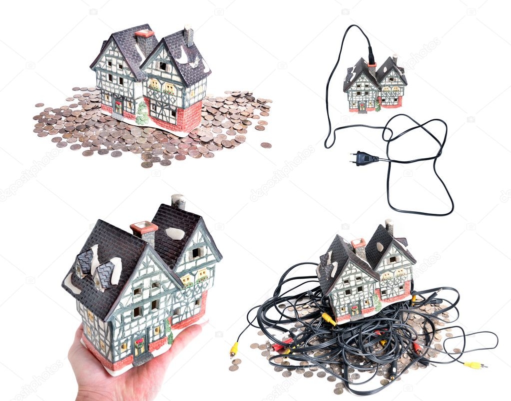 House standing on pile of coins, house on hand, connected house to 220 volt power cord; standing on pile of coins with cables house  Stock Photo #6935420