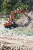 Excavator in the river — Stock Photo