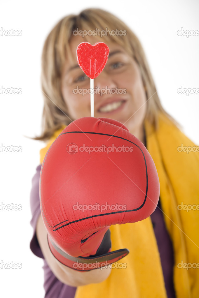 Cheerful woman with boxing gloves holding a lollipop — Stock Photo #6964436