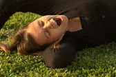 Young Woman Yawning on Grass — Stock Photo
