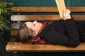 Young Woman Lying on Bench Reading — Stock Photo