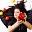 Black angel girl suggesting an apple — Stockfoto