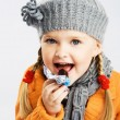 Llittle girl eating chocolate candy — Stock Photo